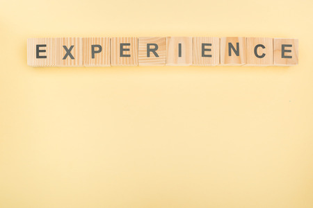 top view of experience lettering made of wooden blocks on yellow background