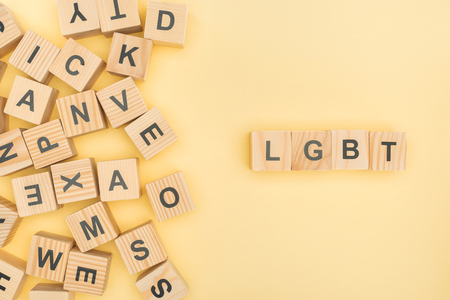 top view of lgbt lettering with wooden cubes on yellow background