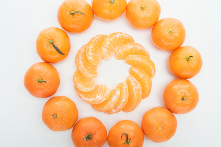 flat lay with circles of peeled tangerine slices and whole tangerines on white background