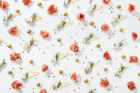 flat lay of sliced pears with blue cheese and rosemary twigs near green olives and tasty prosciutto on white background Фото со стока