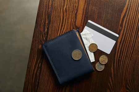 top view of wallet with credit card, coins and cheque on wooden table