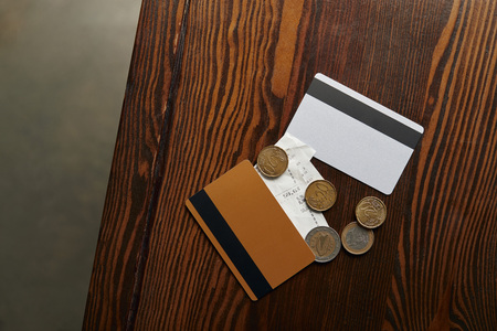 top view of credit cards, coins, cheque on wooden table