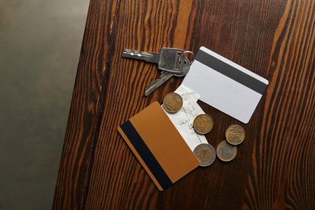 top view of credit cards, coins, cheque and keys on wooden table