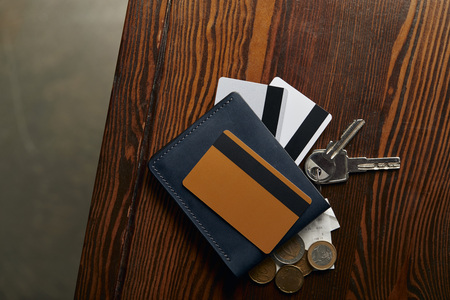 top view of credit cards , coins, cheque and keys on wooden surface