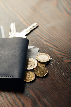 selective focus of leather wallet, keys, cheque and coins on wooden table Stock Photo - 117896510