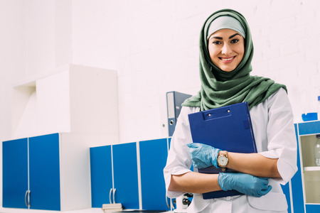 female muslim scientist holding clipboard and looking at camera in laboratory with copy space Stock fotó