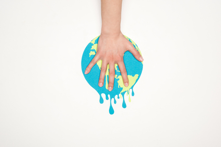cropped view of female hand on paper cut melting globe on white background, global warming concept