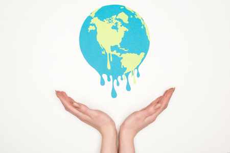 cropped view of woman holding open hands under paper cut melting globe on white background, global warming concept Stock Photo