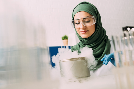 female muslim scientist in goggles during experiment with dry ice in laboratory