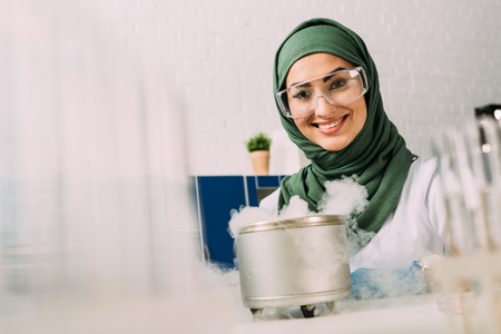smiling female muslim scientist looking at camera during experiment with dry ice in laboratory 写真素材