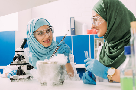 smiling female muslim scientists experimenting with microscope and dry ice in chemical laboratory Stock Photo