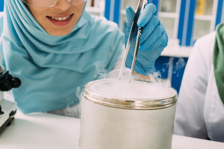partial vie of female muslim scientist holding tweezers during experiment with dry ice in laboratory