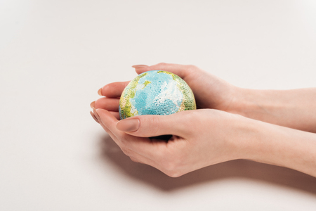 cropped view of female hands with globe model on white background, global warming concept Stock Photo