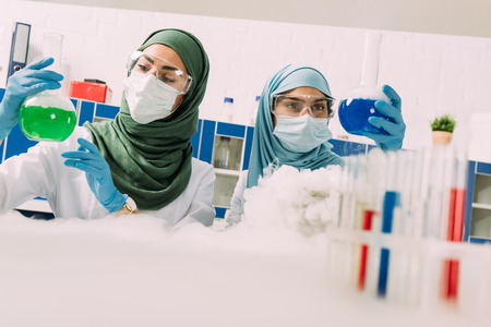 female muslim scientists in medical masks holding flasks while experimenting with dry ice in chemical laboratory