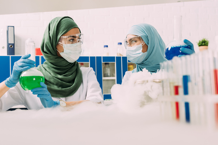 female muslim scientists holding flasks while experimenting with dry ice in chemical laboratory