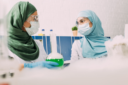 female muslim scientists with flask looking at each other while experimenting with dry ice in chemical laboratory