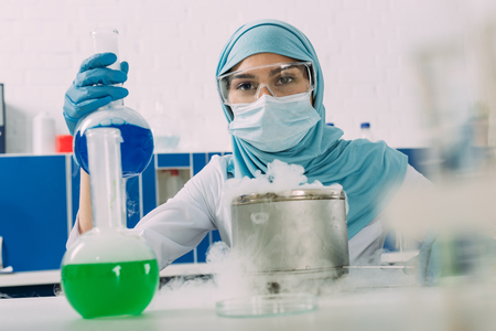 female muslim scientist holding flask during experiment with dry ice in chemical laboratory