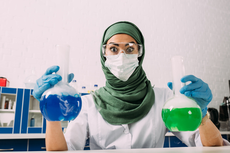 surprised female muslim scientist looking at camera and holding flasks during experiment in chemical laboratory