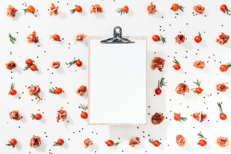 top view of blank clipboard with cherry tomatoes, leaves, spices and prosciutto