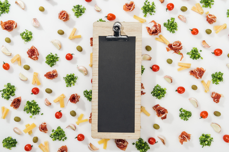 clipboard among olives, prosciutto, greenery, cut cheese, garlic cloves and cherry tomatoes Stock Photo
