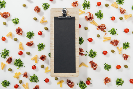 top view of clipboard among olives, prosciutto, greenery, cut cheese and cherry tomatoes