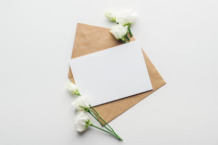 top view of eustoma and envelope with empty card on grey background