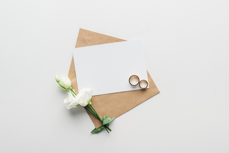 top view of envelope with empty card, flowers and golden wedding rings on grey background