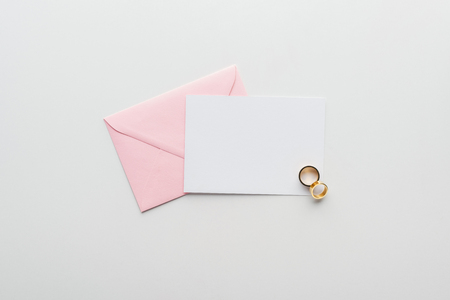 top view of empty card with pink envelope and golden wedding rings on grey background