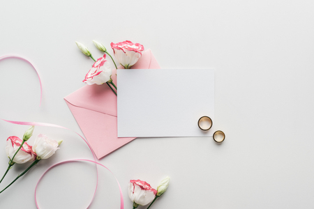top view of empty card with pink envelope, flowers, silk ribbon and golden wedding rings on grey background Stock Photo