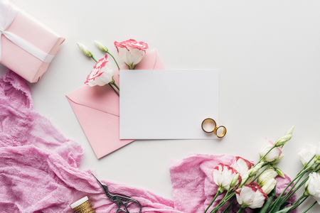 top view of empty card with pink envelope, flowers, cloth, wrapped gift, scissors and golden wedding rings on white background