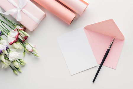 top view of pink envelope with empty card and ink pen, flowers, wrapped gift, rolls of paper on grey background Stock Photo