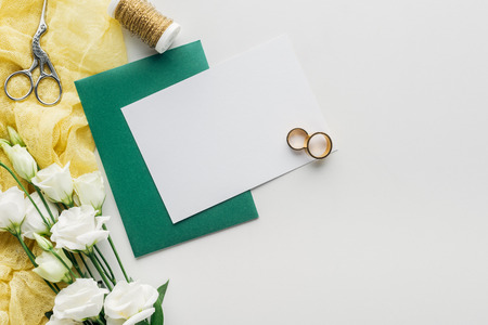 top view of empty card with green envelope, flowers, cloth, spool of thread, scissors and golden wedding rings on grey background