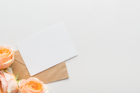 top view of empty blank with brown envelope and pink roses on grey background Zdjęcie Seryjne