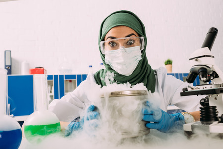 shocked female muslim scientist holding pot with dry ice during experiment in laboratory Stock Photo