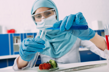 female muslim scientist holding test tubes during experiment with vegetables in laboratory