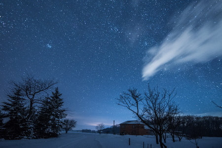 starry dark sky and house in carpathian mountains at night in winter Imagens