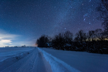 starry dark sky and snowy road in carpathian mountains at night in winter
