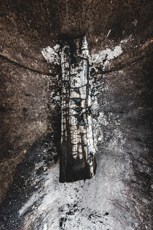 top view of burnt wooden log covered with white ash