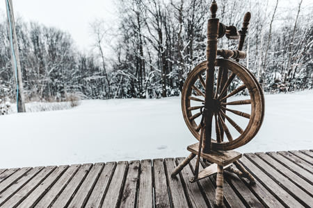 vintage loom on textured wooden planks with winter forest on background