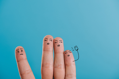 cropped view of fingers taking selfie isolated on blue