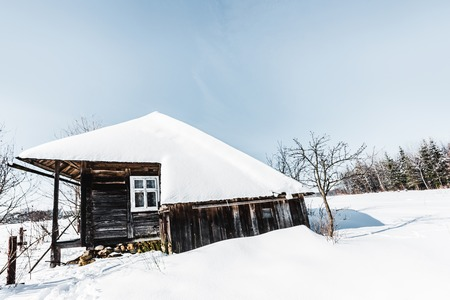 old wooden house with snow in winter carpathian mountains