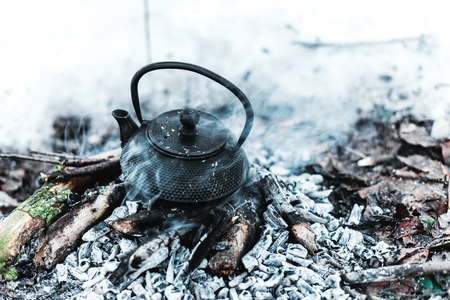 boiling kettle with steam on firewood and ash in winter forest