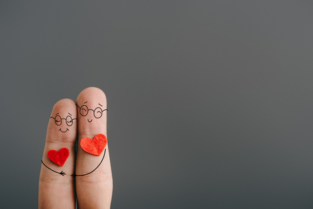 cropped view of happy couple of fingers with hearts hugging isolated on grey, valentines day concept