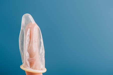 partial view of finger with condom isolated on blue, contraception concept