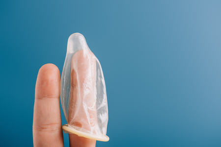 cropped view of fingers with condom isolated on blue, contraception concept