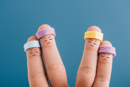cropped view of two dissatisfied couples of sporty fingers in headbands isolated on blue