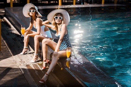 attractive pin up women in swimsuits relaxing at poolside with cocktails Stok Fotoğraf