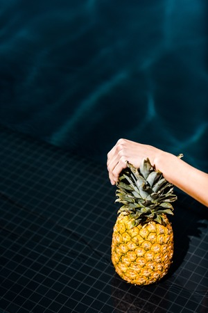 partial view of woman posing with fresh pineapple near swimming pool