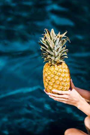partial view of girl posing holding fresh pineapple near swimming pool