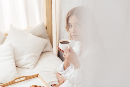 selective focus of young woman holding coffee cup and having breakfast in bed